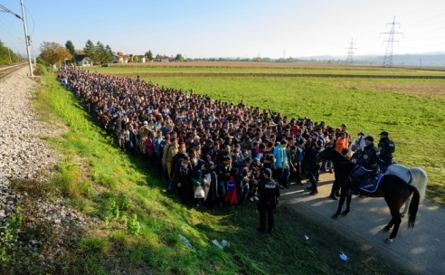 Police escort migrants and asylum seekers as they walk to a refugee centre after crossing the Croatian-Slovenian border near Rigonce on October 24, 2015. Bulgaria, Romania and Serbia threatened to close their borders if EU countries stopped accepting migrants, as European leaders prepared for a mini summit on the continent's worst refugee crisis since World War II. AFP PHOTO / JURE MAKOVEC        (Photo credit should read Jure Makovec/AFP/Getty Images)